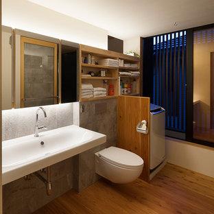 На фото: туалеты в стиле модернизм с открытыми фасадами, светлыми деревянными фасадами, инсталляцией, черно-белой плиткой, керамогранитной плиткой, белыми стенами, светлым паркетным полом, раковиной с несколькими смесителями, столешницей из искусственного камня и бежевым полом