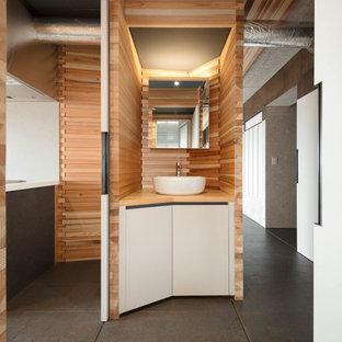 Exemple d'un petit WC et toilettes tendance avec un sol en liège, un plan de toilette en bois et un sol noir.