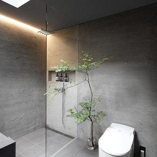 Inredning av ett industriellt litet grå grått toalett, med en toalettstol med hel cisternkåpa, grå kakel, grå väggar, skiffergolv, ett integrerad handfat, bänkskiva i betong och grått golv
