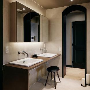 東京23区の中くらいのミッドセンチュリースタイルのおしゃれなトイレ・洗面所 (ベージュの壁、ベージュの床、ベージュのタイル、磁器タイル、磁器タイルの床、ベッセル式洗面器、人工大理石カウンター、ベージュのカウンター) の写真