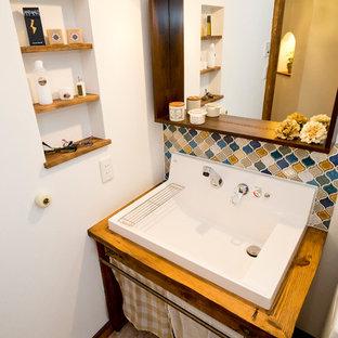 Пример оригинального дизайна: туалет с открытыми фасадами, темными деревянными фасадами, унитазом-моноблоком, разноцветной плиткой, керамогранитной плиткой, белыми стенами, полом из ламината, настольной раковиной, столешницей из дерева и разноцветным полом