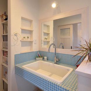 他の地域の北欧スタイルのおしゃれなトイレ・洗面所 (白い壁、オーバーカウンターシンク、タイルの洗面台、グレーの床、青い洗面カウンター) の写真