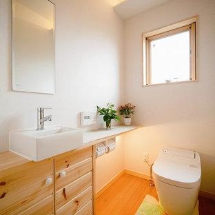 Diseño de aseo de estilo zen con armarios tipo mueble, puertas de armario blancas, sanitario de una pieza, paredes blancas, suelo de contrachapado y suelo marrón