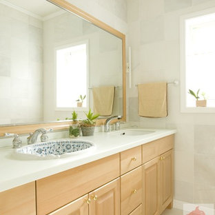 Idée de décoration pour un grand WC et toilettes tradition avec un placard avec porte à panneau encastré, des portes de placard en bois brun, un carrelage blanc, des carreaux de porcelaine, un mur blanc, un sol en carrelage de porcelaine, une vasque, un plan de toilette en surface solide, un sol blanc et un plan de toilette rose.