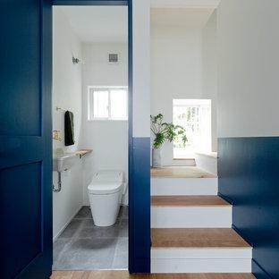 大阪のコンテンポラリースタイルのおしゃれなトイレ・洗面所 (青い壁、コンクリートの床、壁付け型シンク、グレーの床) の写真
