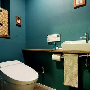 東京23区のエクレクティックスタイルのおしゃれなトイレ・洗面所 (青い壁、ベッセル式洗面器、木製洗面台、茶色い床、ブラウンの洗面カウンター) の写真