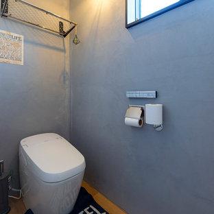 他の地域のインダストリアルスタイルのおしゃれなトイレ・洗面所 (グレーの壁、無垢フローリング、茶色い床) の写真