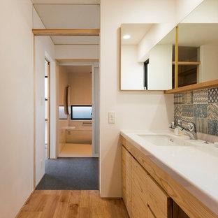 На фото: туалет в современном стиле с фасадами цвета дерева среднего тона, синей плиткой, белыми стенами, паркетным полом среднего тона, врезной раковиной, коричневым полом и белой столешницей
