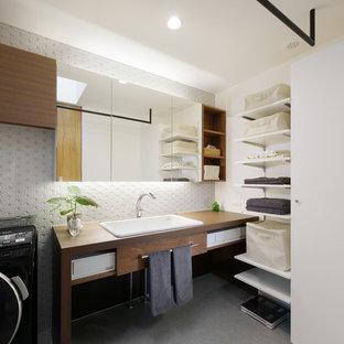 Skandinavisk inredning av ett mellanstort toalett, med öppna hyllor, vit kakel, porslinskakel, vita väggar, ett undermonterad handfat och grått golv