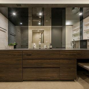 モダンスタイルのおしゃれなトイレ・洗面所 (濃色木目調キャビネット、ベージュのタイル、ベージュの壁、アンダーカウンター洗面器、ベージュの床、黒い洗面カウンター) の写真