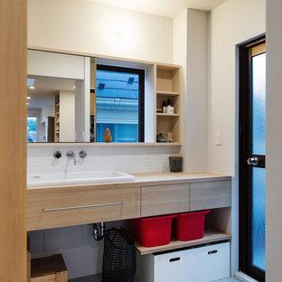 Réalisation d'un WC et toilettes nordique de taille moyenne avec un placard sans porte, des portes de placard en bois brun, un carrelage blanc, des carreaux de porcelaine, un mur blanc, un sol en linoléum, un lavabo posé, un plan de toilette en bois et un sol gris.