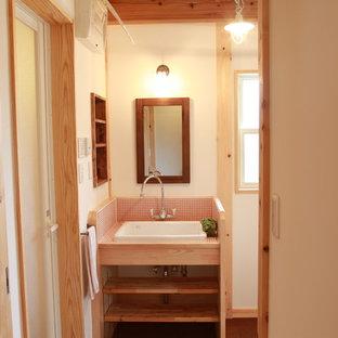 Стильный дизайн: туалет в стиле кантри с розовой плиткой, белыми стенами, пробковым полом, врезной раковиной и коричневым полом - последний тренд