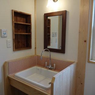 Идея дизайна: туалет в стиле кантри с розовой плиткой, белыми стенами, пробковым полом, врезной раковиной и коричневым полом
