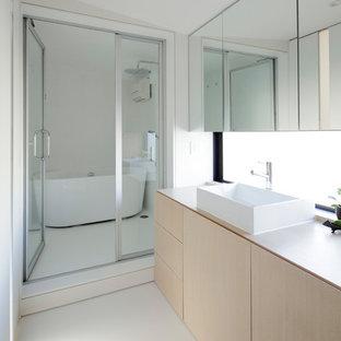 Moderne Gästetoilette mit hellen Holzschränken, Wandtoilette mit Spülkasten, weißer Wandfarbe, Vinylboden, Aufsatzwaschbecken, Waschtisch aus Holz, weißem Boden, weißer Waschtischplatte und Kassettenfronten in Tokio