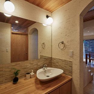 神戸のアジアンスタイルのおしゃれなトイレ・洗面所 (フラットパネル扉のキャビネット、淡色木目調キャビネット、一体型トイレ、緑のタイル、磁器タイル、ベージュの壁、淡色無垢フローリング、コンソール型シンク、木製洗面台、ベージュの床、ベージュのカウンター、造り付け洗面台、板張り天井) の写真