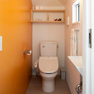 This is an example of a medium sized modern cloakroom in Yokohama with beaded cabinets, light wood cabinets, a one-piece toilet, orange walls, plywood flooring, a submerged sink and beige floors.