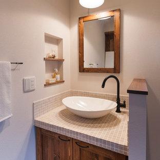 Imagen de aseo de estilo zen con armarios con paneles empotrados, puertas de armario de madera oscura, paredes blancas, lavabo sobreencimera y encimera de azulejos