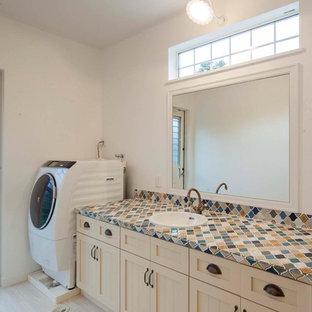 Неиссякаемый источник вдохновения для домашнего уюта: туалет в стиле шебби-шик с фасадами в стиле шейкер, бежевыми фасадами, белыми стенами, полом из винила, накладной раковиной, столешницей из плитки и серым полом