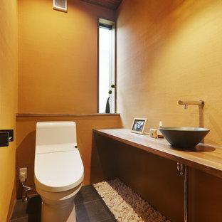 Diseño de aseo asiático con paredes marrones, lavabo sobreencimera y suelo negro