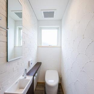 Modelo de aseo moderno con paredes blancas, lavabo encastrado, encimera de madera, suelo gris y encimeras marrones