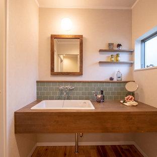 他の地域の小さいカントリー風おしゃれなトイレ・洗面所 (白い壁、無垢フローリング、オーバーカウンターシンク、茶色い床、緑のタイル、木製洗面台、ブラウンの洗面カウンター) の写真