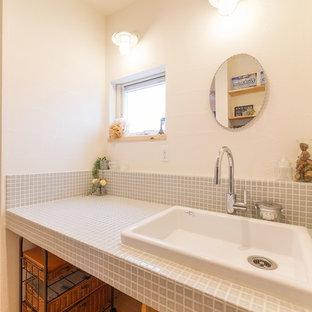 Imagen de aseo asiático con paredes blancas, suelo de madera en tonos medios, lavabo encastrado, encimera de azulejos y suelo marrón