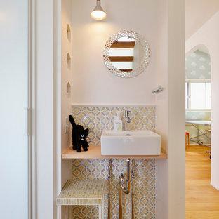 Idéer för små minimalistiska toaletter, med mellanmörkt trägolv, ett fristående handfat, vita väggar och orange golv