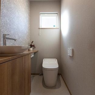 他の地域の中くらいのモダンスタイルのおしゃれなトイレ・洗面所 (フラットパネル扉のキャビネット、中間色木目調キャビネット、グレーの壁、ベッセル式洗面器、木製洗面台、グレーの床、ブラウンの洗面カウンター) の写真