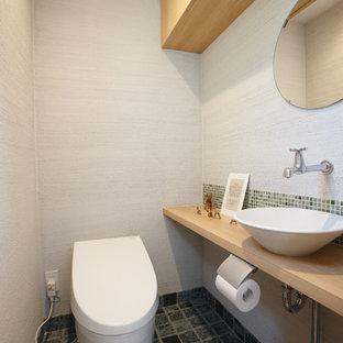 Ejemplo de aseo de estilo zen con paredes blancas, lavabo sobreencimera, encimera de madera, suelo gris y encimeras beige