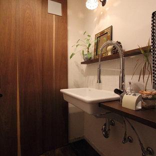 Стильный дизайн: туалет в стиле современная классика с раздельным унитазом, белой плиткой, керамогранитной плиткой, белыми стенами, полом из винила, раковиной с несколькими смесителями, столешницей из дерева и коричневым полом - последний тренд