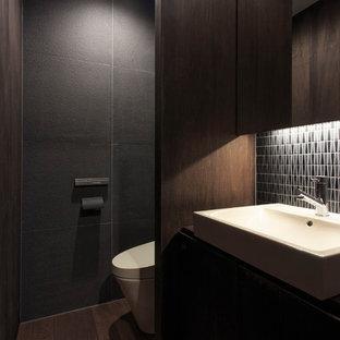 Diseño de aseo de estilo zen con armarios con paneles lisos, puertas de armario de madera en tonos medios, paredes grises, suelo de madera oscura, lavabo sobreencimera y suelo marrón