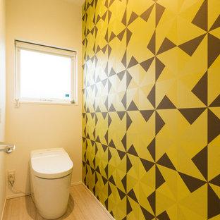 他の地域のモダンスタイルのおしゃれなトイレ・洗面所 (マルチカラーの壁、塗装フローリング、ベージュの床) の写真