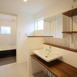 Idée de décoration pour un WC et toilettes minimaliste avec un mur blanc, un sol en vinyl et un sol gris.