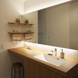 Свежая идея для дизайна: маленький туалет в стиле лофт с фасадами с декоративным кантом, темными деревянными фасадами, белыми стенами, светлым паркетным полом, монолитной раковиной и коричневым полом - отличное фото интерьера