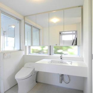 他の地域のおしゃれなトイレ・洗面所 (ガラス扉のキャビネット、白いキャビネット、一体型トイレ、白い壁、リノリウムの床、アンダーカウンター洗面器、人工大理石カウンター、グレーの床、白い洗面カウンター、フローティング洗面台、塗装板張りの天井、塗装板張りの壁) の写真