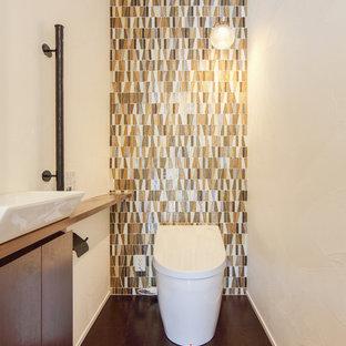 Ejemplo de aseo de estilo zen, de tamaño medio, con paredes blancas, lavabo sobreencimera, encimera de madera y suelo marrón