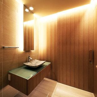 Новый формат декора квартиры: большой туалет в стиле модернизм с унитазом-моноблоком, коричневой плиткой, цементной плиткой, коричневыми стенами, мраморным полом, стеклянной столешницей и бежевым полом