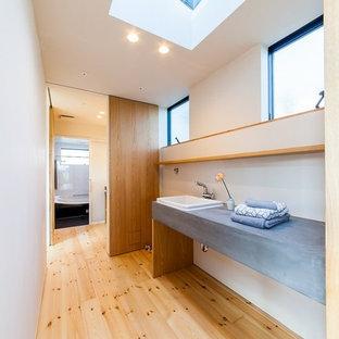Пример оригинального дизайна: туалет в восточном стиле с белыми стенами, светлым паркетным полом, накладной раковиной, столешницей из бетона и бежевым полом