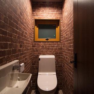 他の地域のアジアンスタイルのおしゃれなトイレ・洗面所 (茶色い壁、グレーの床、一体型トイレ、壁付け型シンク) の写真