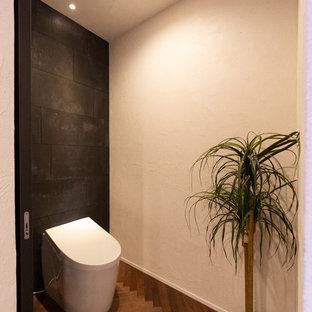 Exemple d'un WC et toilettes moderne avec un carrelage noir, des carreaux de béton, un mur noir, un sol en bois foncé et un sol marron.