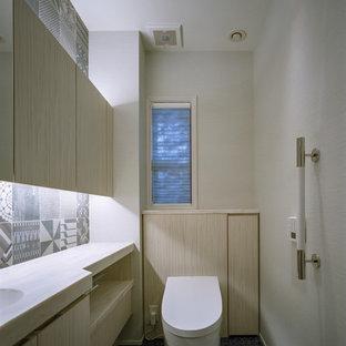 神戸の北欧スタイルのおしゃれなトイレ・洗面所 (インセット扉のキャビネット、ベージュのキャビネット、一体型トイレ、モノトーンのタイル、白い壁、クッションフロア、アンダーカウンター洗面器、人工大理石カウンター、青い床、ベージュのカウンター) の写真