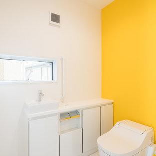 他の地域のモダンスタイルのおしゃれなトイレ・洗面所 (フラットパネル扉のキャビネット、白いキャビネット、黄色い壁、ベッセル式洗面器、白い床、白い洗面カウンター) の写真