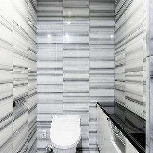 横浜の中くらいのコンテンポラリースタイルのおしゃれなトイレ・洗面所 (黒いキャビネット、黒いタイル、大理石タイル、グレーの壁、大理石の床、人工大理石カウンター、グレーの床、白い洗面カウンター) の写真