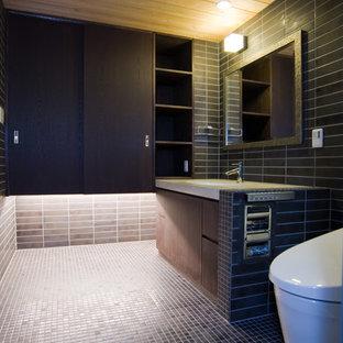 На фото: маленькие туалеты в стиле лофт с коричневыми фасадами, унитазом-моноблоком, керамогранитной плиткой, коричневыми стенами, полом из мозаичной плитки, врезной раковиной, коричневым полом, бежевой столешницей, плоскими фасадами, черной плиткой и столешницей из искусственного камня