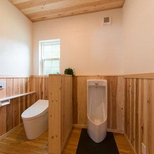 Свежая идея для дизайна: туалет в стиле кантри с писсуаром, белыми стенами и паркетным полом среднего тона - отличное фото интерьера