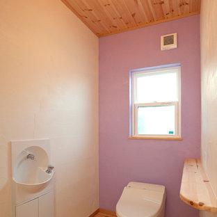 Свежая идея для дизайна: туалет в стиле кантри с унитазом-моноблоком, фиолетовыми стенами, паркетным полом среднего тона, подвесной раковиной и столешницей из дерева - отличное фото интерьера