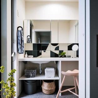 他の地域のモダンスタイルのおしゃれなトイレ・洗面所 (オープンシェルフ、白いタイル、黒いタイル、白い壁、一体型シンク、グレーの床、白い洗面カウンター) の写真