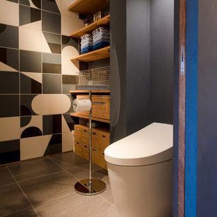 東京都下のアジアンスタイルのおしゃれなトイレ・洗面所 (一体型トイレ、ベージュのタイル、グレーのタイル、白いタイル、セメントタイル、黒い壁、茶色い床) の写真