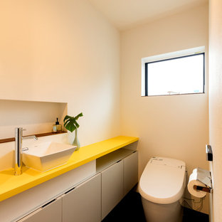 他の地域の中くらいのモダンスタイルのおしゃれなトイレ・洗面所 (白いキャビネット、一体型トイレ、白い壁、オーバーカウンターシンク、人工大理石カウンター、黒い床、黄色い洗面カウンター、クロスの天井、壁紙) の写真