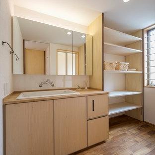 Cette photo montre un WC et toilettes asiatique avec un placard à porte plane, des portes de placard en bois clair, un mur blanc, un sol en bois brun, un lavabo posé, un plan de toilette en bois, un sol marron et un plan de toilette beige.